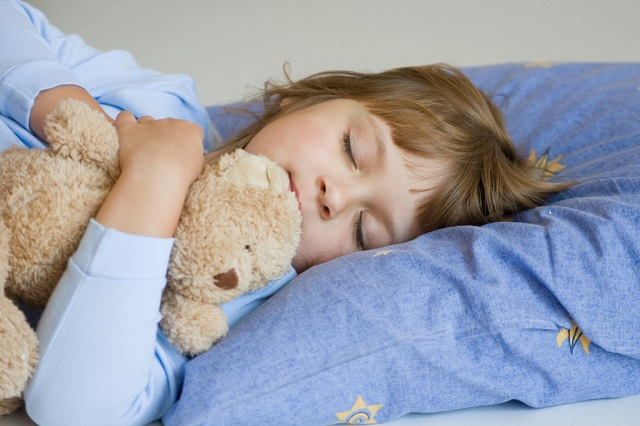 cute little girl sleeping on a blue pillow
